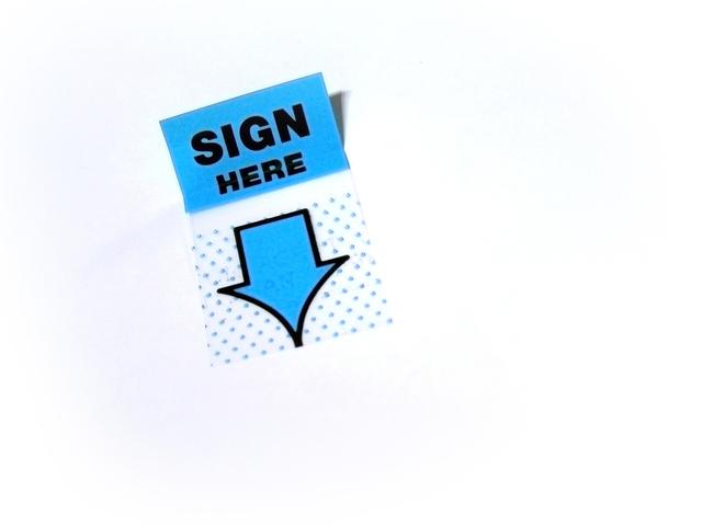lepík ukazující na místo podpisu úvěrové smlouvy